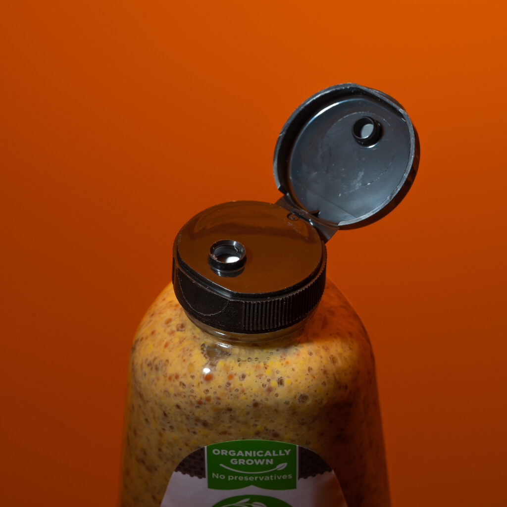 Open bottle of mustard with no tamper seal in place