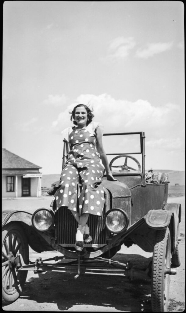Woman sitting on old car, early 1900s